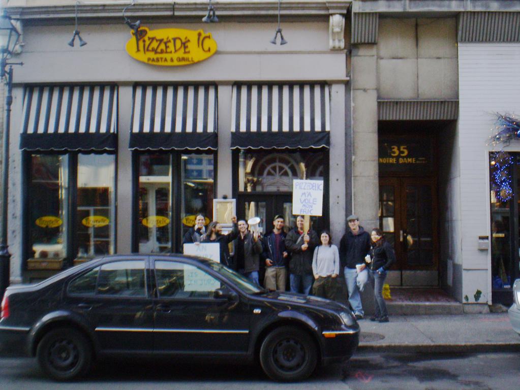des gens avec des pancartes devant la vitrien du Pizzédéic