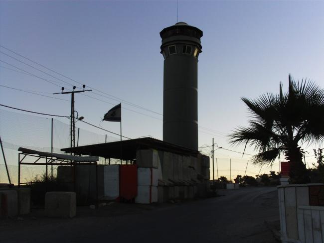 photo où on voit une tour militaire israélienne, entourée de blocs de bétons, un palmier sur le côté droit de la route-entrée