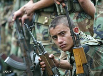 photo de certains des paramilitaires: un jeune homme tenant une mitrailleuse AK47 regarde de côté la caméra. Il a les cheveux très courts et un regard un peu froid ou sérieux