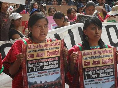Deux jeunes femmes du village, vêtues de leur costume traditionnelle rouge, tiennent des affiches-posters au sujet des gens assassinés. Il y a une manifestation en appui derrière elles.