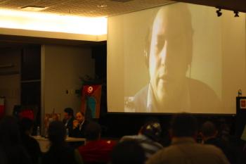 Photo: derrières des têtes d'une partie de l'auditoire ; de loin deux conférenciers à une table ; derrière l'écran géant vidéo-conférence du 3e conférencier. Derrière la table des peintures pour l'occasion sont placées sur des chevets.