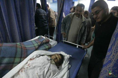 Dans un hôpital bondé, des hommes regardent, l'air abasourdi, un enfant palestinien mort sur un lit.