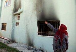 Une femme, portant un foulard rouge et un gillet de cotton chaud, pointe vers sa maison blanche noircie par un feu.