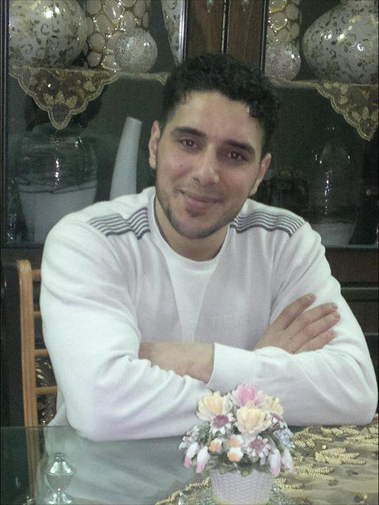 photo du jeune homme, cheveux courts noirs, bras croisés sur une table de cuisine, arborant un léger sourire.
