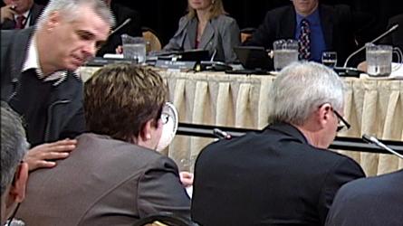 Photo : des fonctionnaires sont autour d'une table, en réunion. Le protagoniste est en train de placer la tarte vers le visage de la fonctionnaire. La photo est juste avant le contact et que toute personne réalise qu'un événement se produit.