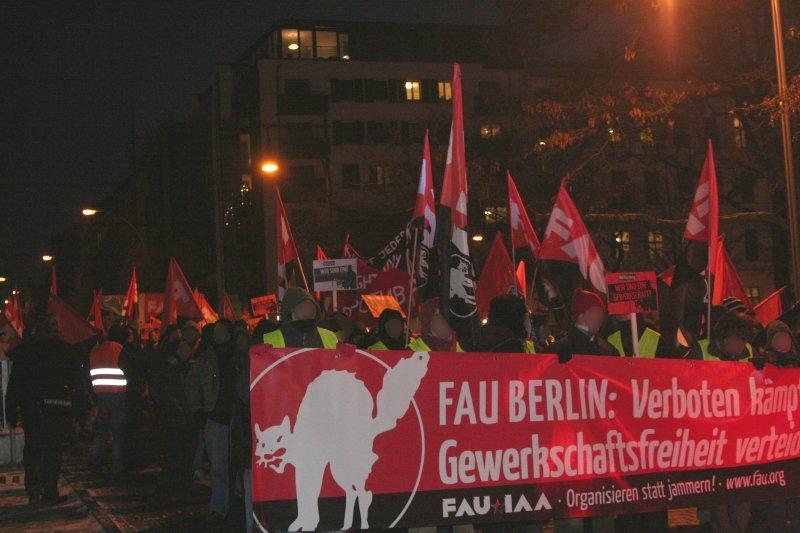 Manifestation vue de face, de la FAU. La banderole semble en allemand: logo d'un chat blanc sur une banderole noir et rouge [anarchiste donc]